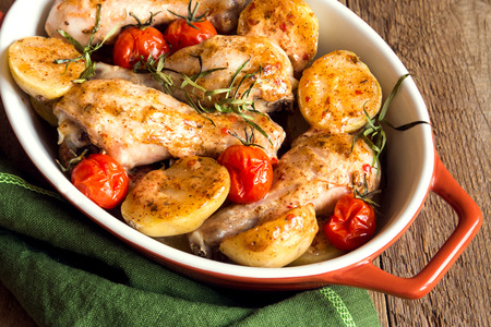 grilled vegetables: Oven baked chicken legs with vegetables (tomatoes, potatoes), herbs and spices in baking dish on rustic wooden background