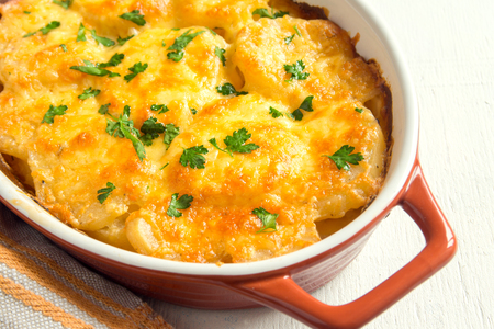 Potato gratin with cream, cheese and parsley in baking dish
