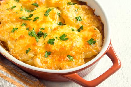 patatas: Patatas gratinadas con crema, queso y perejil en el plato para hornear Foto de archivo