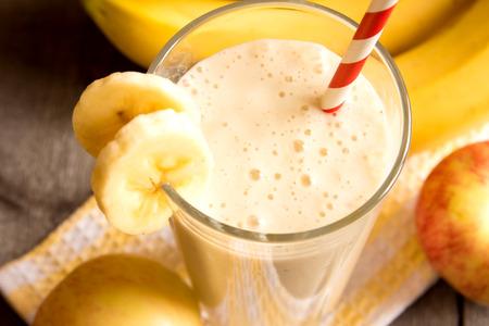 banane: Smoothie aux fruits (banane, pomme, pêche) sur fond de bois