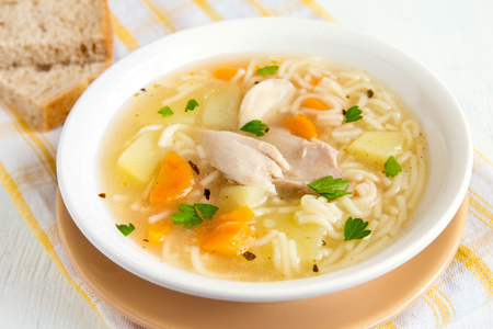 broth: Chicken soup with noodles and vegetables in white bowl