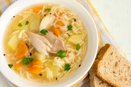 Chicken soup with noodles and vegetables in white bowl