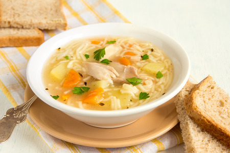 meat dish: Chicken soup with noodles and vegetables in white bowl
