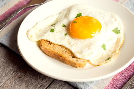 Gebakken ei op brood voor het ontbijt op plaat en rustieke tafel