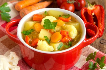 sopa de pollo: Sopa de verduras con ingredientes zanahoria coliflor patata perejil pimienta coles de tomate de cerca