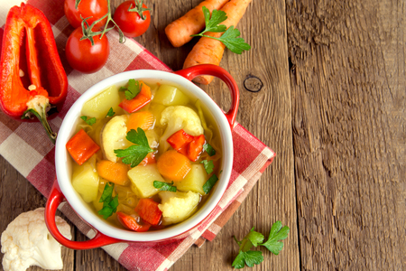 Vegetable soup with ingredients carrot cauliflower potato parsley pepper cabbage tomato over rustic wooden background with copy space Foto de archivo