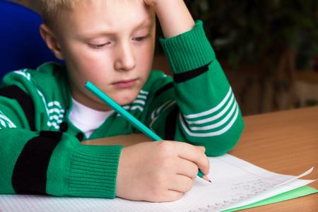 Tired boring boy doing his difficult school homework