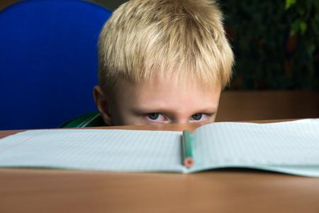 Moe saai jongen wil niet zijn moeilijke huiswerk doen Stockfoto