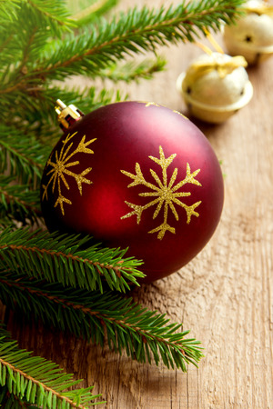 glass christmas tree ornament: Red Christmas ball on wooden background with branches of green fir, copy space