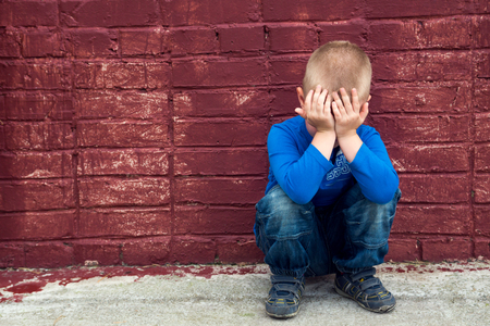 Depressed abused poor crying little child (boy, kid) sitting near big red brick wall