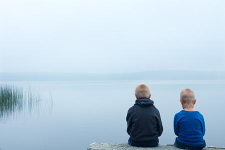 mirada triste: Dos niños tristes (niños, hermanos) sentado solo por el lago en un día de niebla, vista posterior