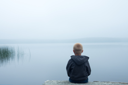 solitude: sad child sitting alone by lake in a foggy day, back view