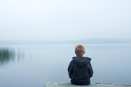 verdrietig kind zit alleen door meer in een mistige dag, achteraanzicht