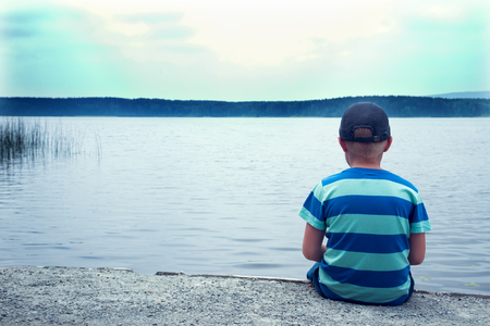 child alone: sad child sitting alone at the lake on a cloudy day, back view