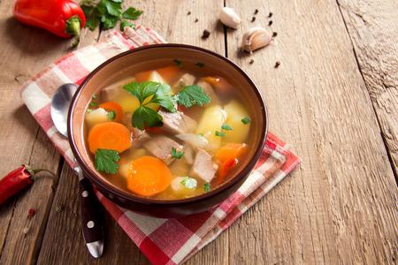 소박한 나무 배경 위에 그릇에 파 슬 리와 고기와 야채 수프를 닫습니다 스톡 콘텐츠