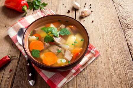 Meat and vegetables soup with parsley in bowl over rustic wooden background close up Foto de archivo