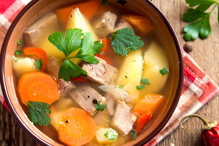 Meat and vegetables soup with spices and parsley in bowl over rustic wooden background close up