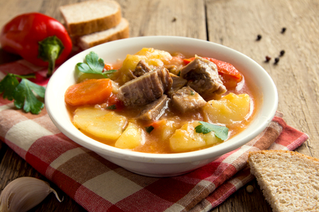 lunch table: Tasty winter stew with meat and vegetables in bowl with ingredients over rustic wooden table