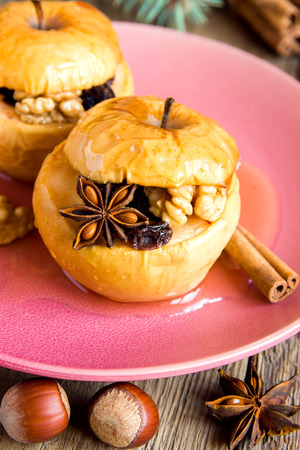 pine  fruit: Christmas baked apples stuffed with dried fruit, nuts and honey on pink plate with cinnamon, anise stars and pine branches over wooden background