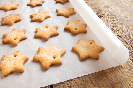 baking christmas cookies: Homemade gingerbread cookies (stars) on baking paper and rustic wooden table
