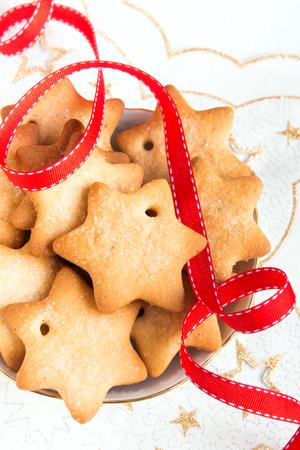 galletas de jengibre: Las galletas de pan de jengibre de Navidad en servilleta blanca con estrellas y cinta roja para las vacaciones de invierno Foto de archivo