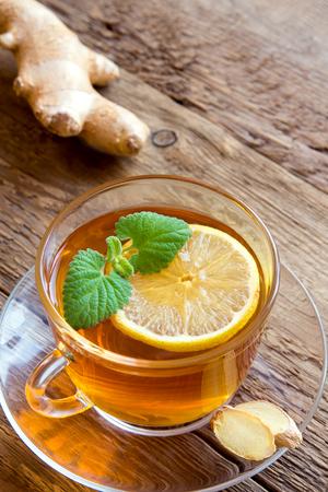 lemon: T� con lim�n, jengibre y hojas de menta en la taza transparente sobre fondo de madera r�stica