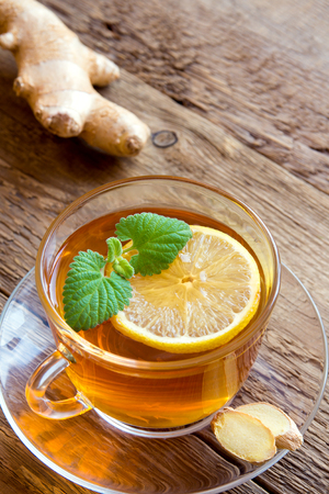 lemon: Tea with lemon, ginger and mint leaves in transparent cup over rustic wooden background