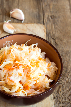 rustic food: Sauerkraut in ceramic bowl on rustic wooden table with garlic, traditional rustic winter food Stock Photo