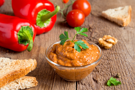 roasted pepper dip with nuts and bread in glass bowl over rustic wooden background closeup Reklamní fotografie