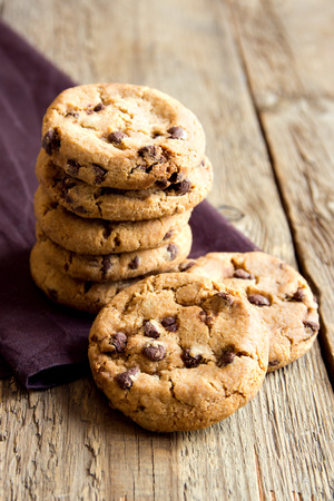 american cuisine: Chocolate chip cookies on brown napkin and rustic wooden table