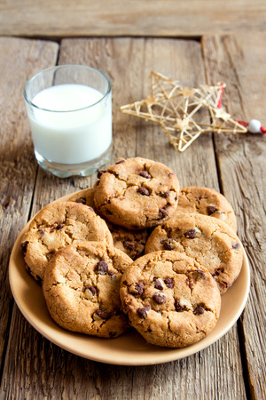 Chocolate chip cookies with milk and christmas star on rustic wooden table Banco de Imagens