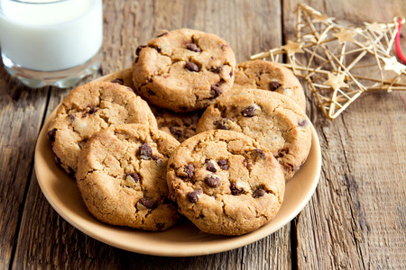 biscuits: Chocolate chip cookies with milk and christmas star on rustic wooden table Stock Photo