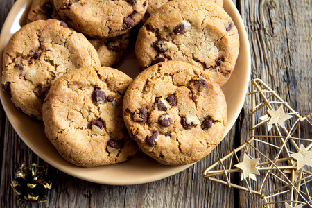 Chocolate chip cookies  on plate with christmas star on rustic wooden table