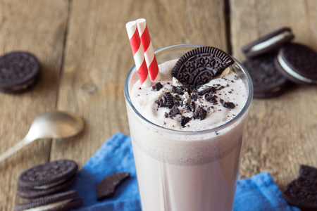 Homemade milkshake (chocolate smoothie) with cookies on rustic wooden table close up Foto de archivo