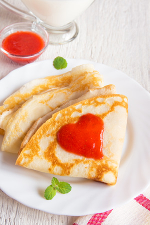 desayuno romantico: Pancakes with strawberry jam heart shape for traditional romantic breakfast, valentine day concept