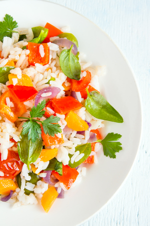 red cooked: Colorful rice and vegetable salad on white plate close up Stock Photo