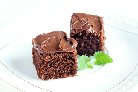 bisquit: Chocolate mini cakes with chocolate icing and mint on white plate close up