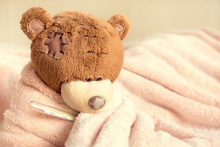 Sick teddy bear with thermometer in bed