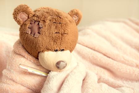 oso de peluche enfermo con el termómetro en la cama