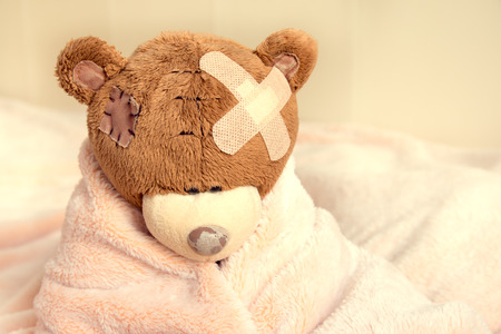 sick teddy bear: Sick teddy bear with patch in bed