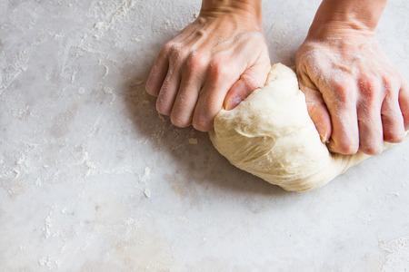 Handen kneed het deeg op de snijplank voor zelfgemaakte bakkerij