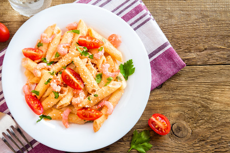 Penne pasta with shrimps, tomato sauce, parsley and grated parmesan cheese over rustic wooden background Stock Photo