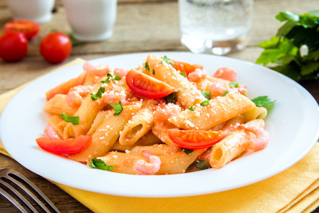 grated parmesan cheese: Penne pasta with shrimps, tomato sauce, parsley and grated parmesan cheese over rustic wooden background Stock Photo