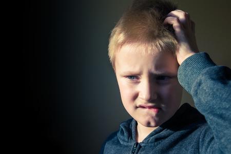 preguntando: Boy (adolescente, niño) rascarse la cabeza confundido en problemas sobre fondo oscuro con espacio de copia