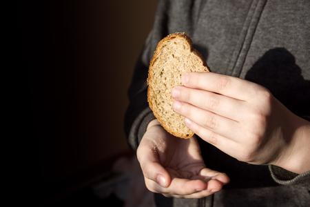 arme kinder: Stück Brot in Kinderhände. Hunger und helfen Konzept.
