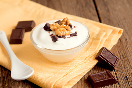 stracciatella: Plain Organic Yogurt with Chocolate and Nuts in Bowl. Homemade dessert on rustic wooden table close up. Stock Photo