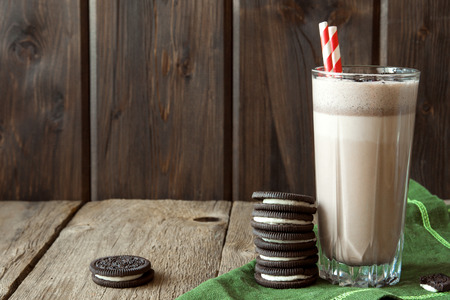 Homemade milkshake (chocolate smoothie) with cookies on rustic wooden table with copy space