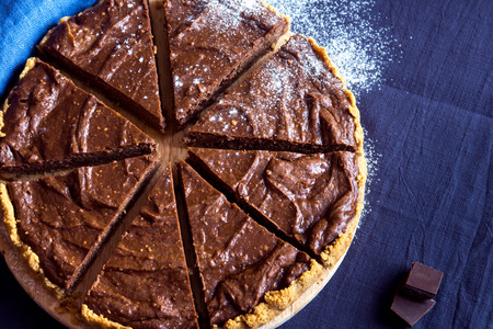 relaxation background: Homemade chocolate cheesecake (pie) with sugar powder on linen background close up