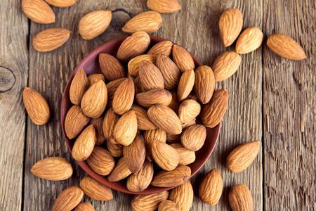 Almonds over rustic wooden background, healthy vegetarian snack