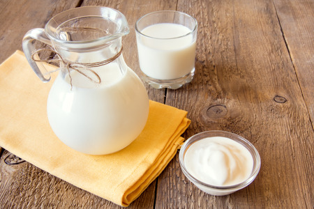 Calcium dairy fresh products: milk and sour cream (yogurt)  on napkin and wooden table, close up, horizonal, copy space